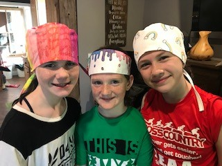 Students showing off their hand-drawn scrub cap and headband designs