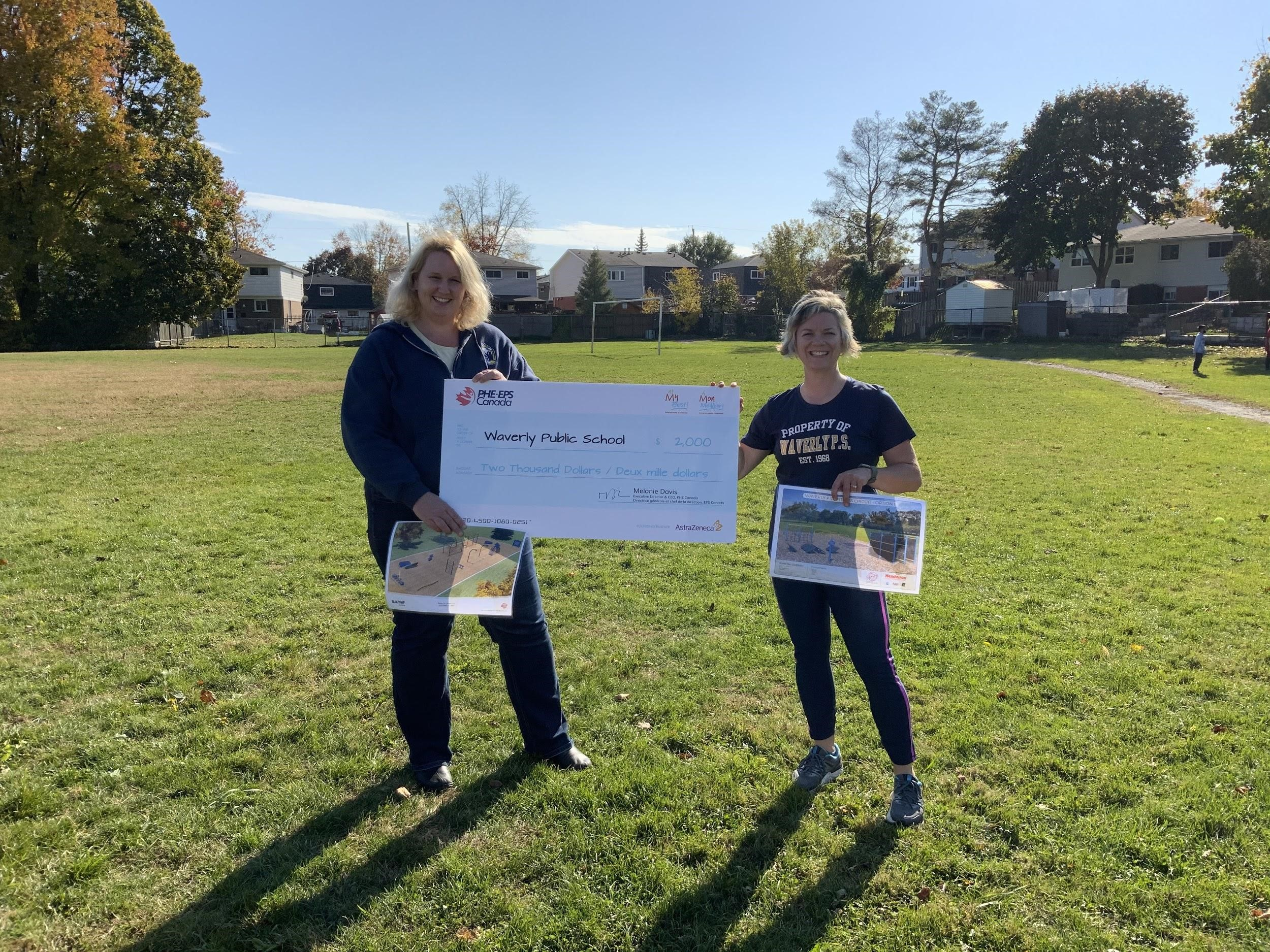 Waverly Public School Principal Amanda Chapman and Physical Education Teacher Sherri Parr with the $2000 grant check from At My Best.